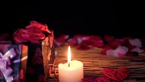 Lycklig valentindag med längd i fot räknat av gåvaaskar, stearinljusbränningen och blommakronblad