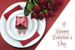 Lycklig valentindag som äter middag tabellinställningen, med röda hjärtor, gåvan och röda rosor Arkivfoto
