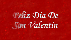 Lycklig valentins dagtext i spanska Feliz Dia De San Valentin vänder till damm från vänstert på röd bakgrund Arkivfoton