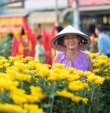 Lycklig vietnamesisk kvinna som säljer blommor arkivfoton