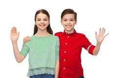 Lycklig vinkande hand för pojke och för flicka Royaltyfri Fotografi