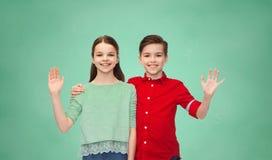 Lycklig vinkande hand för pojke och för flicka Fotografering för Bildbyråer