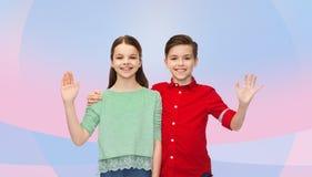 Lycklig vinkande hand för pojke och för flicka Royaltyfri Bild
