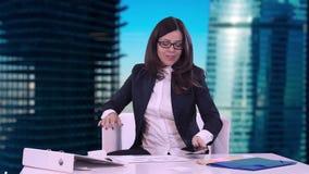 Lycklig visar när du ler ung brunett i en affärsdräkt tummen på kameran Hon sitter i kontoret bak ett skrivbord på arkivfilmer