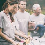 Lycklig volontär som ser donationasken royaltyfri fotografi