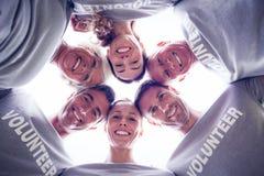Lycklig volontärfamilj som ner ser på kameran Arkivfoto