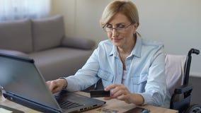Lycklig vuxen kvinna i skrivande in kortnummer för rullstol på bärbara datorn som direktanslutet shoppar lager videofilmer