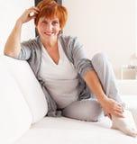 Lycklig vuxen kvinna på soffan Fotografering för Bildbyråer
