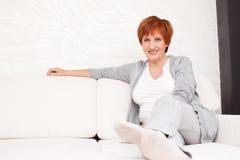 Lycklig vuxen kvinna på soffan Royaltyfri Bild