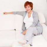 Lycklig vuxen kvinna på soffan Arkivbild