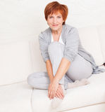 Lycklig vuxen kvinna på soffan Royaltyfri Foto