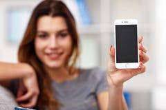 Lycklig vuxen kvinna som hemma använder telefonen i vardagsrummet Arkivbild