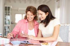 Lycklig vuxen moder och dotter som scrapbooking Arkivbilder