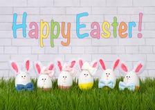 Lyckliga ägg för påskkanin i gräs royaltyfria bilder