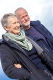 Lyckliga äldre höga par som går på stranden royaltyfria foton