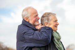 Lyckliga äldre höga par som går på stranden arkivfoto