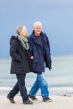 Lyckliga äldre höga par som går på stranden royaltyfri bild