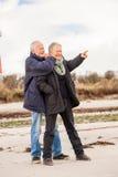 Lyckliga äldre höga par som går på stranden royaltyfri fotografi