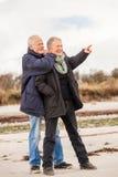 Lyckliga äldre höga par som går på stranden arkivbilder