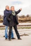 Lyckliga äldre höga par som går på stranden arkivbild