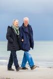 Lyckliga äldre höga par som går på stranden royaltyfri foto