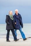 Lyckliga äldre höga par som går på stranden royaltyfria bilder