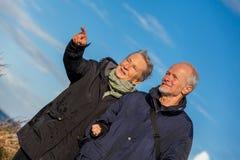 Lyckliga äldre höga par som går på stranden fotografering för bildbyråer