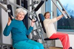 Lyckliga äldre kvinnor som utarbetar på idrottshallen royaltyfri bild