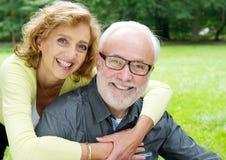 Lyckliga äldre par som ler och visar affektion