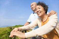 Lyckliga äldre pensionärpar i parkera Arkivfoto