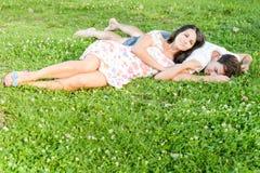 Lyckliga älska barnpar som kopplar av utomhus fotografering för bildbyråer
