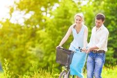 Lyckliga älska Caucasian par som har gyckel som rider tillsammans cykelOu Fotografering för Bildbyråer