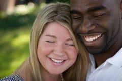 Lyckliga älska mångkulturella par som kramar och ler Fotografering för Bildbyråer