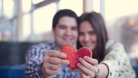 Lyckliga älska par i kafét som skrattar och att dricka te använda minnestavlan för gyckel Datera först arkivfilmer