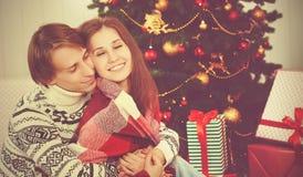 Lyckliga älska par i omfamning värme på julgranen Royaltyfri Fotografi