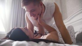 Lyckliga älska par i säng och att se, le och tryckande sig på arkivfilmer