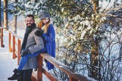 Lyckliga älska par som går i den snöig vinterskogen som spenderar jul, semestrar tillsammans Royaltyfria Foton
