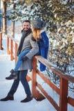 Lyckliga älska par som går i den snöig vinterskogen som spenderar jul, semestrar tillsammans Royaltyfri Fotografi