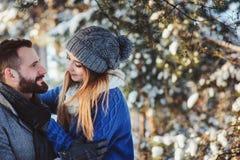 Lyckliga älska par som går i den snöig vinterskogen som spenderar jul, semestrar tillsammans Arkivbild