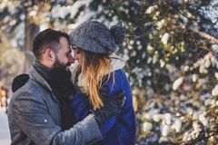 Lyckliga älska par som går i den snöig vinterskogen som spenderar jul, semestrar tillsammans Arkivfoton