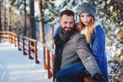 Lyckliga älska par som går i den snöig vinterskogen som spenderar jul, semestrar tillsammans Arkivfoto