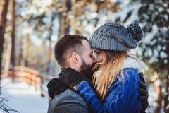 Lyckliga älska par som går i den snöig vinterskogen som spenderar jul, semestrar tillsammans Fotografering för Bildbyråer