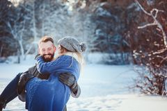 Lyckliga älska par som går i den snöig vinterskogen som spenderar jul, semestrar tillsammans Royaltyfri Bild