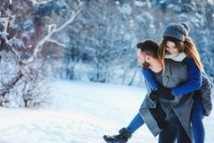 Lyckliga älska par som går i den snöig vinterskogen som spenderar jul, semestrar tillsammans Utomhus- säsongsbetonade aktiviteter Arkivbilder