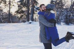 Lyckliga älska par som går i den snöig vinterskogen som spenderar jul, semestrar tillsammans Utomhus- säsongsbetonade aktiviteter Royaltyfri Bild