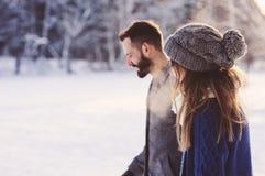 Lyckliga älska par som går i den snöig vinterskogen som spenderar jul, semestrar tillsammans Utomhus- säsongsbetonade aktiviteter Royaltyfria Foton