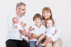 Lyckliga älska par som har gyckel med tre ungar Royaltyfri Foto