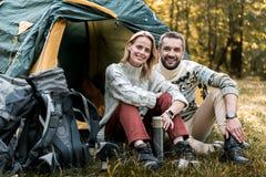Lyckliga älska par som vilar nära tältet i träna arkivbild