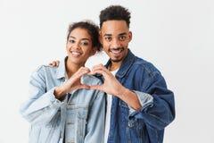 Lyckliga älskvärda afrikanska par i grov bomullstvillskjortor som visar hjärta, undertecknar Royaltyfri Foto