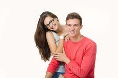Lyckliga älskvärda par som kramar och ler se kameran på vit bakgrund royaltyfri foto